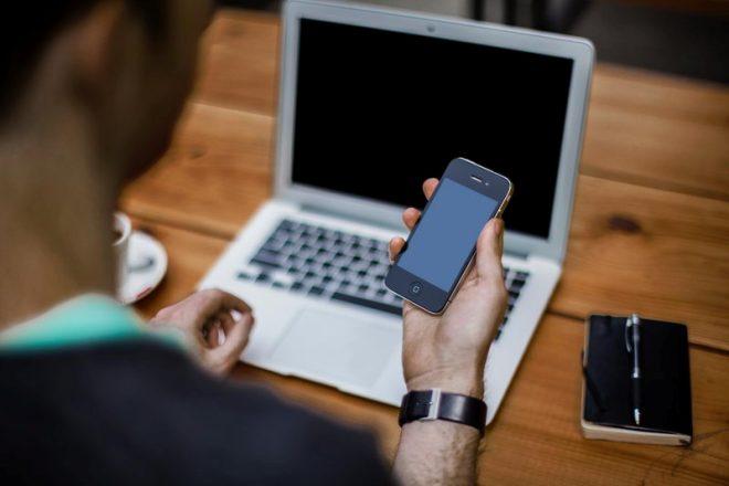 Мужчина с телефоном и ноутбуком
