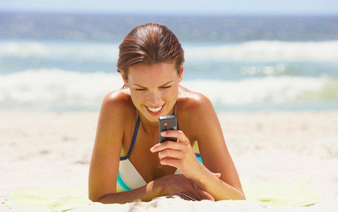 Девушка на пляже с телефоном